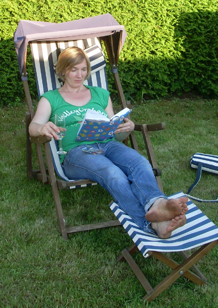 Meine Frau im Liegestuhl auf dem kleinen Rasen direkt hinter dem Haus